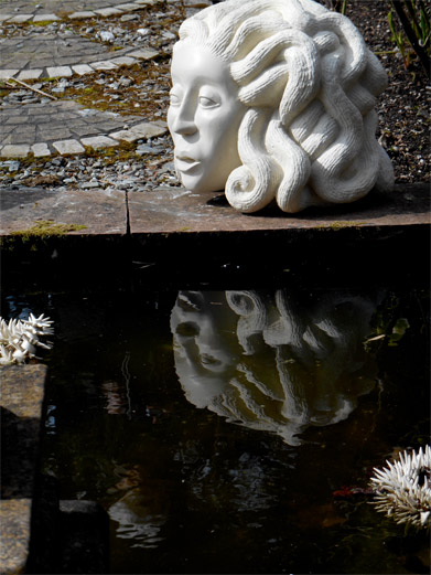 Stone carved head a pond edge with reflection